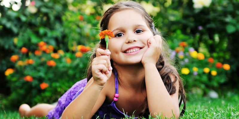 happy young girl children relax lie and have fun on grass with flower